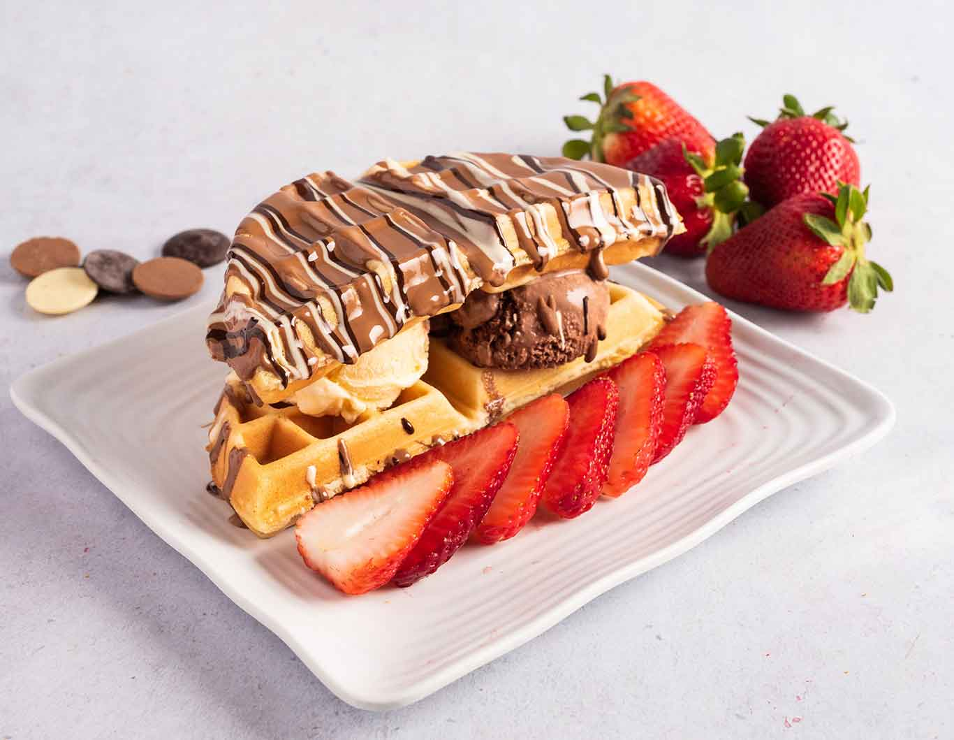 Waffle ice cream sandwich with three types of chocolate drizzles and strawberry slices